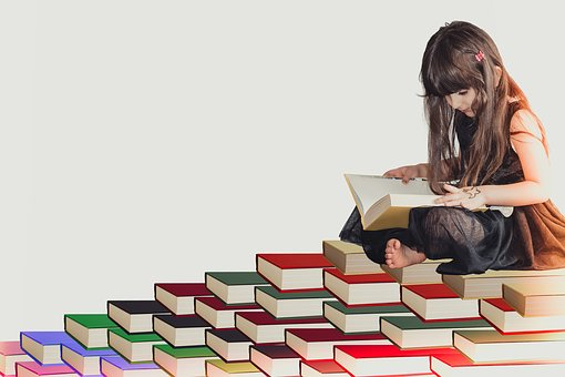 Girl Sitting on Stack of books
